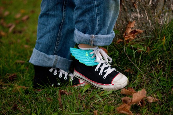 Child with food allergies in sneakers with wings