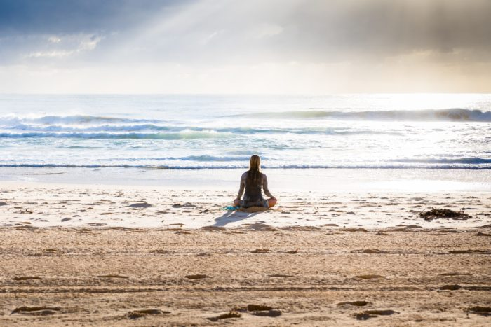 Lady on a beach meditating